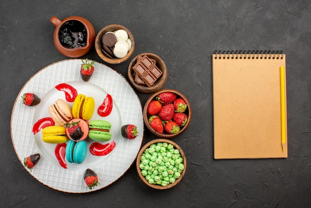 Top view from afar strawberries and macaroons plate of chocolate-covered strawberries french macaroons bowls of sweets around it and notebook with pencil on the table
