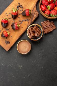 テーブルのまな板にチョコレートで覆われたイチゴの横にチョコレートとイチゴのチョコレートバーと遠くのイチゴからの上面図