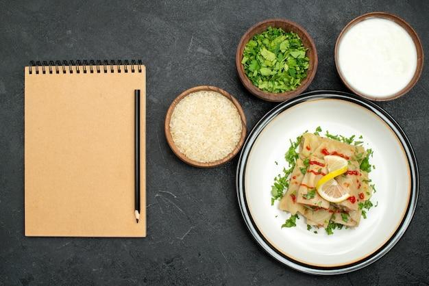 遠くからの上面図食欲をそそる詰め物キャベツとハーブレモンとソースの白いプレートとボウルにライスハーブとサワークリームの横にあるクリームノートの横にある黒いテーブルに鉛筆で