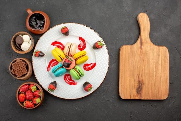 マカロンの遠くの甘い皿プレートと暗い背景の木製まな板の横にあるキャンディーチョコレートイチゴとチョコレートクリームの4つのボウルからの上面図