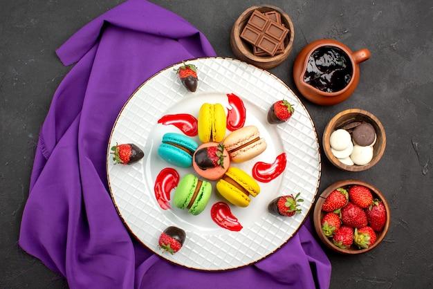 紫色のテーブルクロスにマカロンの白いプレートと暗い表面にキャンディーチョコレートイチゴとチョコレートクリームの4つのボウルの遠くの甘い皿からの上面図