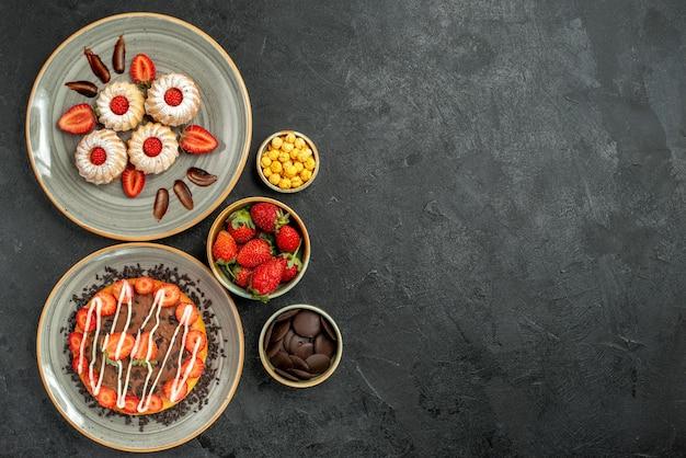 遠くのお菓子とケーキの食欲をそそるクッキーとイチゴとチョコレートのケーキと黒いテーブルの左側にハイゼルナッツチョコレートとイチゴのボウルからの上面図
