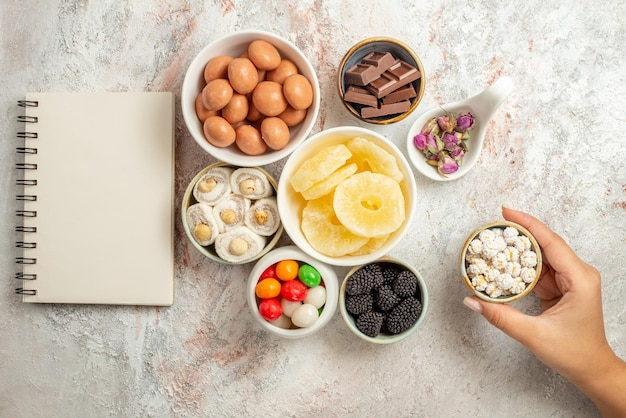 Top view from afar sweets in bowls white notebook next to the bowls of sweets dried fruits and berries in the hand