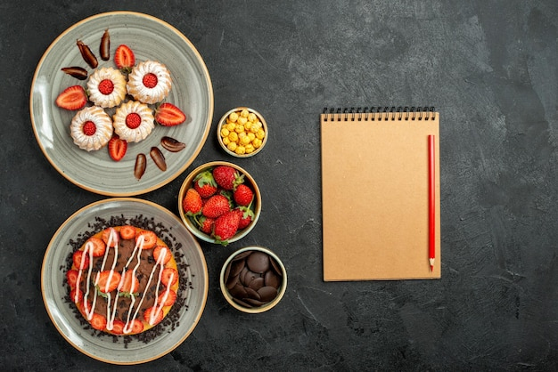 Top view from afar sweets and cake appetizing cookies and cake with strawberry and chocolate and bowls of hizelnuts chocolate and strawberry next to cream notebook and red pencil on the table