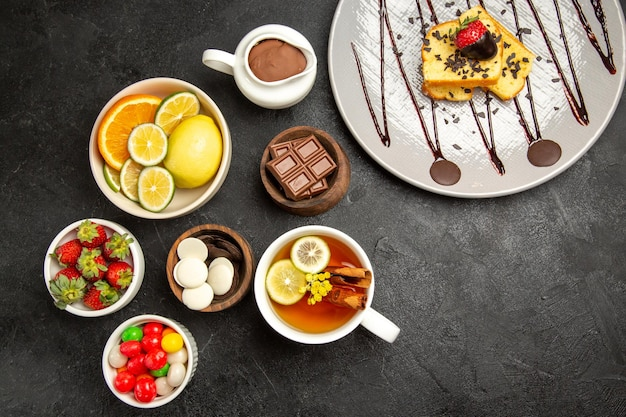 Top view from afar sweets grey plate of cake next to the bowls of citrus fruits chocolate candies strawberries chocolate cream the cup of tea