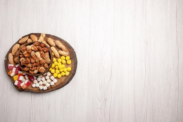 하얀 탁자의 왼쪽에 있는 도마에 있는 사탕 옆에 있는 그릇에 있는 멀리 있는 과자의 꼭대기