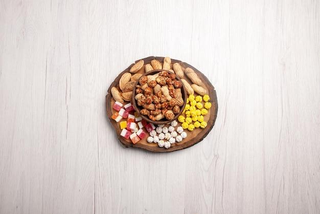Вид сверху издалека сладости в миске сладкий арахис в миске рядом с конфетами на разделочной доске на белом столе