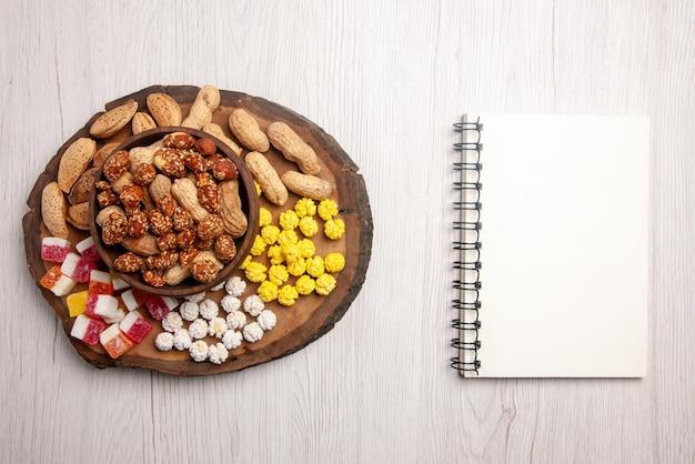 Вид сверху сладости в миске белый блокнот рядом с разделочной доской со сладостями и миской арахиса на белом столе