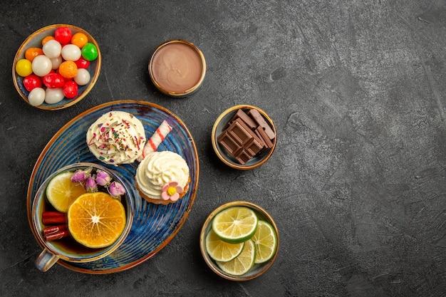 Вид сверху сладости на столе, тарелки с конфетами, шоколад, шоколад, крем и дольки лайма, рядом с тарелкой двух кексов и чашкой травяного чая на столе