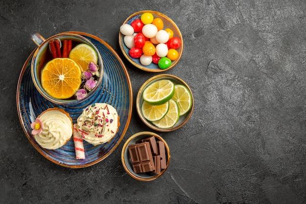 Вид сверху издалека сладости на столе, три миски конфет, шоколад и дольки лайма рядом с синим блюдцем, чашка черного травяного чая и два кекса на столе