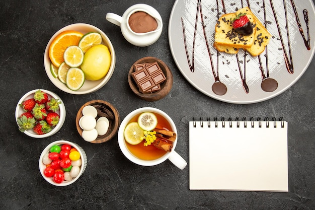 Top view from afar sweets plate of cake next to the bowls of citrus fruits chocolate candies strawberries chocolate cream the cup of tea and white notebook