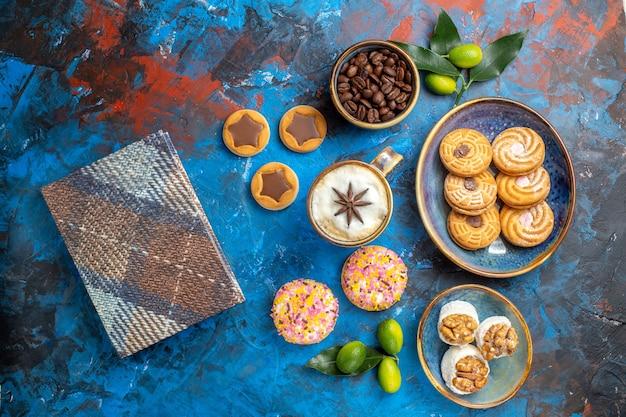 遠いお菓子からの上面図ボウル柑橘系の果物のテーブルクロスで食欲をそそるクッキーコーヒー豆