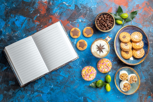 遠いお菓子からの上面図ボウル柑橘系の果物の白いノートに食欲をそそるクッキーコーヒー豆