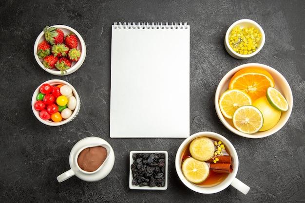 Вид сверху издалека сладости с чаем чашка травяного чая с палочками корицы рядом с белым блокнотом и тарелки конфет шоколадный крем клубника и цитрусовые на столе
