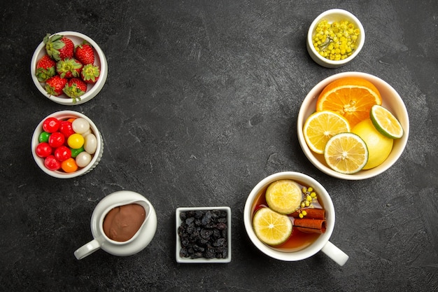 Top view from afar sweets with tea a cup of herbal tea with cinnamon sticks bowls of candies chocolate cream strawberries and citrus fruits on the table