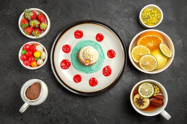 Top view from afar sweets with tea a cup of tea with star anise next to the plate of cupcake and the bowls of herbs citrus fruits chocolate cream strawberries on the table