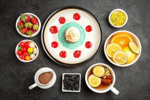 Top view from afar sweets with tea plate of appetizing cupcake next to the cup of herbal tea bowls of chocolate cream strawberries citrus fruits and candies