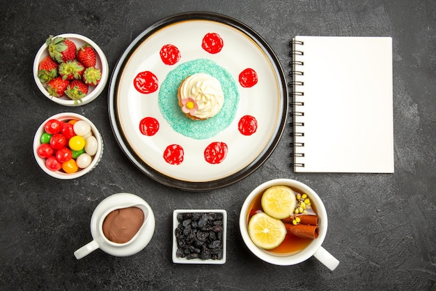 Top view from afar sweets with tea white notebook cupcake with cream a cup of herbal tea with lemon next to the bowls of chocolate cream strawberries and candies