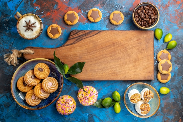 Vista dall'alto da lontano tavola di legno dolci accanto ai diversi dolci biscotti chicchi di caffè