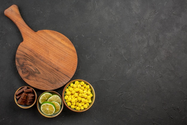 Top view from afar sweets wooden cutting board next to the bowls of chocolate limes and yellow candies on the left side of the table