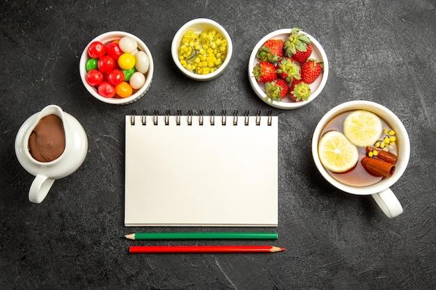 하얀 공책과 연필 옆에 있는 사탕 초콜릿 크림 허브와 딸기의 맛있는 디저트 그릇, 계피를 곁들인 차 한 잔