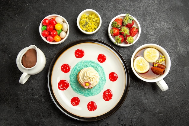 Top view from afar tasty dessert plate of appetizing cupcake the bowls of chocolate cream candies and strawberries and a cup of tea with lemon