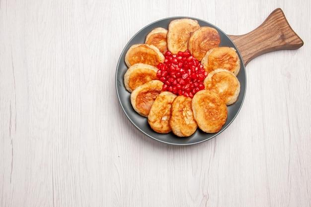 テーブルの上の木製のまな板の上に食欲をそそるパンケーキとザクロの遠くのおいしい皿プレートからの上面図