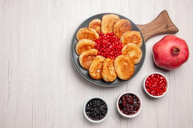 Vista dall'alto da lontano gustoso piatto di melograno ciotole di marmellata e piatto di appetitose frittelle e melograno sul tagliere di legno sul tavolo