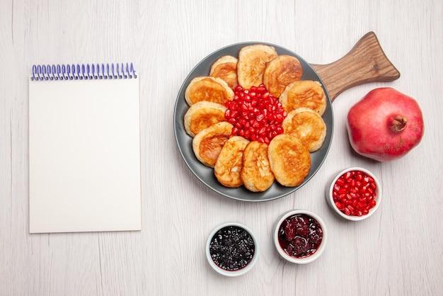 Vista dall'alto da lontano gustoso piatto ciotole di melograno di marmellata quaderno bianco e piatto di appetitose frittelle e melograno sul tagliere di legno sul tavolo