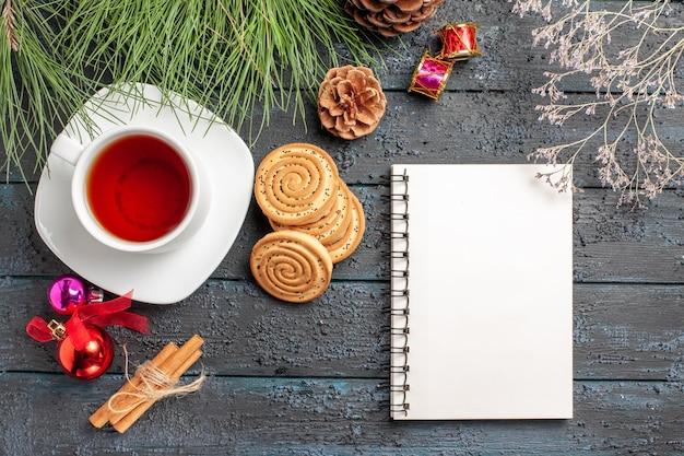시나몬 옆에 콘과 크리스마스 장난감이 있는 멀리 차 가문비나무의 꼭대기 전망은 접시와 흰색 공책에 차 한 잔을 꽂습니다.
