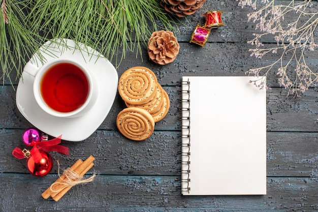 Top view from afar tea spruce tree with cones and christmas toys next to the cinnamon sticks a cup of tea on the saucer and white notebook