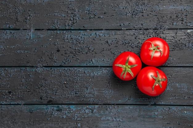 Vista dall'alto da lontano tre pomodori tre pomodori maturi su un tavolo di legno