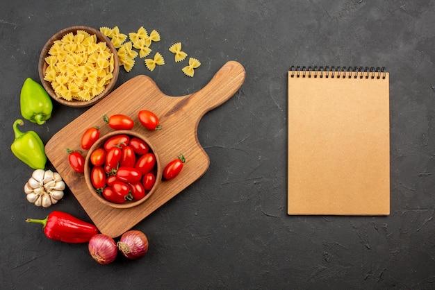 遠くのトマトとスパイスからの上面図ピーマン玉ねぎにんにくとパスタのボウルは木の板のトマトのボウルとテーブルのクリームのノートの横にあります
