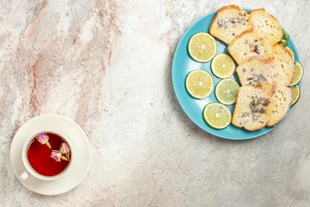 케이크의 파란색 접시 옆에 있는 접시에 홍차 한 잔과 테이블에 얇게 썬 라임이 있는 멀리 떨어진 접시의 위쪽 전망