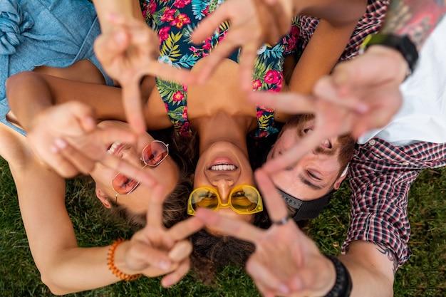 Vista dall'alto dall'alto sulla compagnia giovane felice elegante colorato di amici sdraiati sull'erba nel parco, uomo e donna che hanno divertimento insieme