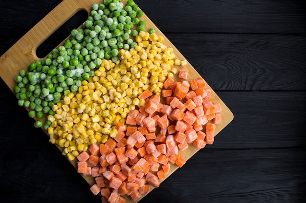 Top view of frozen vegetables in the brown cutting board