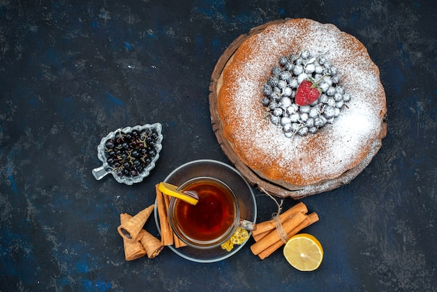 Una torta alla frutta vista dall'alto, deliziosa e rotonda, formata con blu fresco, frutti di bosco e insieme a una tazza di tè sulla torta di zucchero dolce