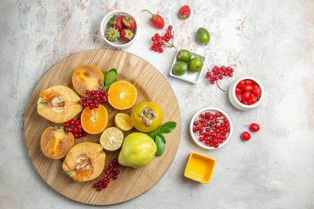 Vista dall'alto composizione nella frutta mele pere e altri frutti su scrivania bianca frutta fresca matura