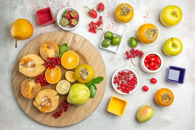 Vista dall'alto composizione nella frutta mele pere e altri frutti sulla tavola bianca frutta fresca matura