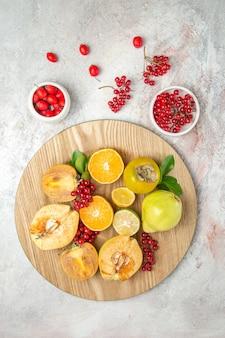 Vista dall'alto composizione di frutta mele pere e altri frutti sulla tavola bianca frutta fresca matura
