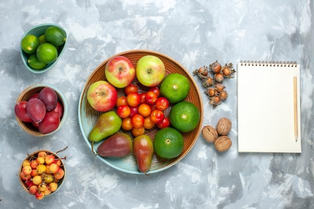 Vista dall'alto composizione di frutta mele pere noci mandarini e prugne sullo scrittorio bianco.