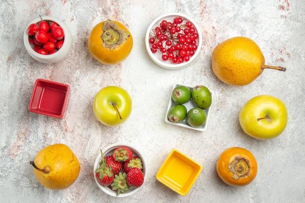 白いテーブルの上のさまざまな新鮮な果物の上面図