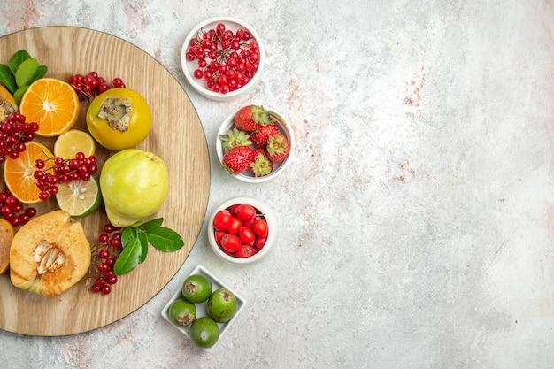 Vista superiore della composizione nella frutta frutti diversi sulla tavola bianca leggera frutti di bosco freschi maturi
