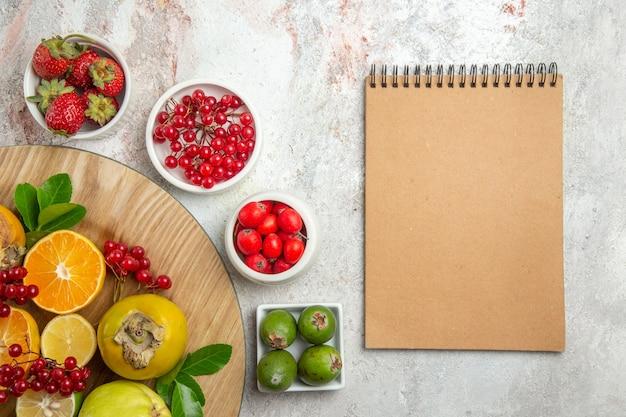 Вид сверху фруктовая композиция, разные фрукты на белом столе, ягоды, свежие фрукты, спелые
