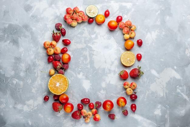 上面図フルーツ組成レモンプラムとチェリーが白い机の上に並んでいますフルーツ熟した新鮮なまろやかなビタミン