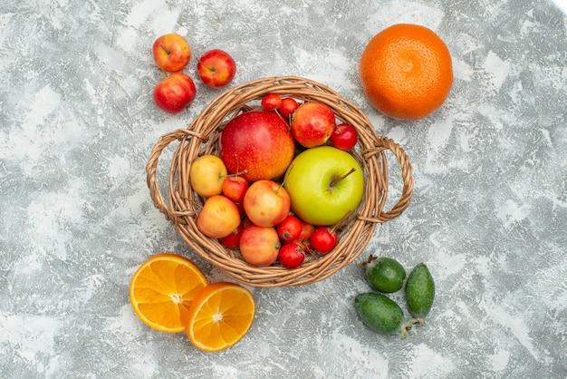 Vista dall'alto composizione di frutta prugne e mele su uno spazio bianco chiaro