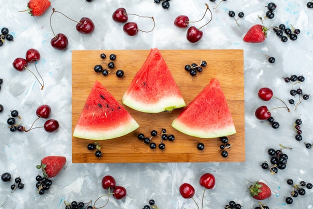 A top view fruit composition sliced watermelon along with fresh fruits on white, fruit color mellow