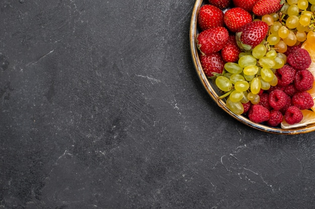 Top view fruit composition strawberries grapes raspberries and tangerines inside tray on dark-grey space