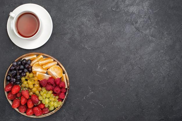 Vista dall'alto composizione di frutta fragole uva lamponi e mandarini con una tazza di tè sullo scrittorio scuro