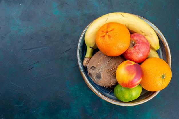 짙은 파란색 책상에 있는 상위 뷰 과일 구성 귤 바나나 사과와 코코넛